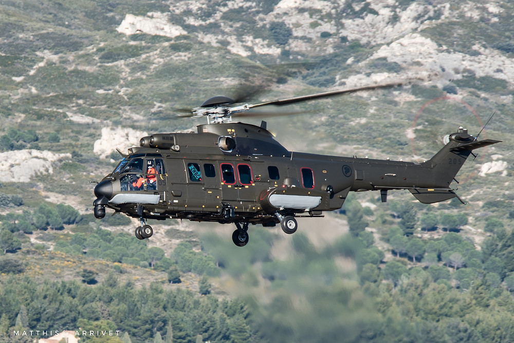 A Republic of Singapore Air Force H225M helicopter is flying in front of mountains