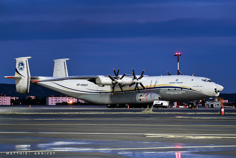 An antonov An22 cargo airplane is parked on an airport by night