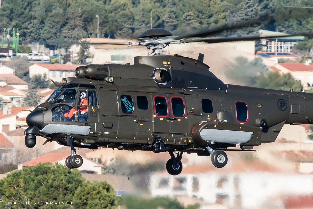 Close up of a Republic of Singapore Air Force H225M flying near a city.