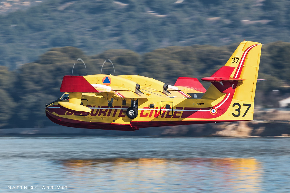 A Canadair Cl-415 Superscooper is landing on a lake to refill water for a training mission