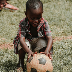 Child%20smiling%20with%20a%20soccer%20ba