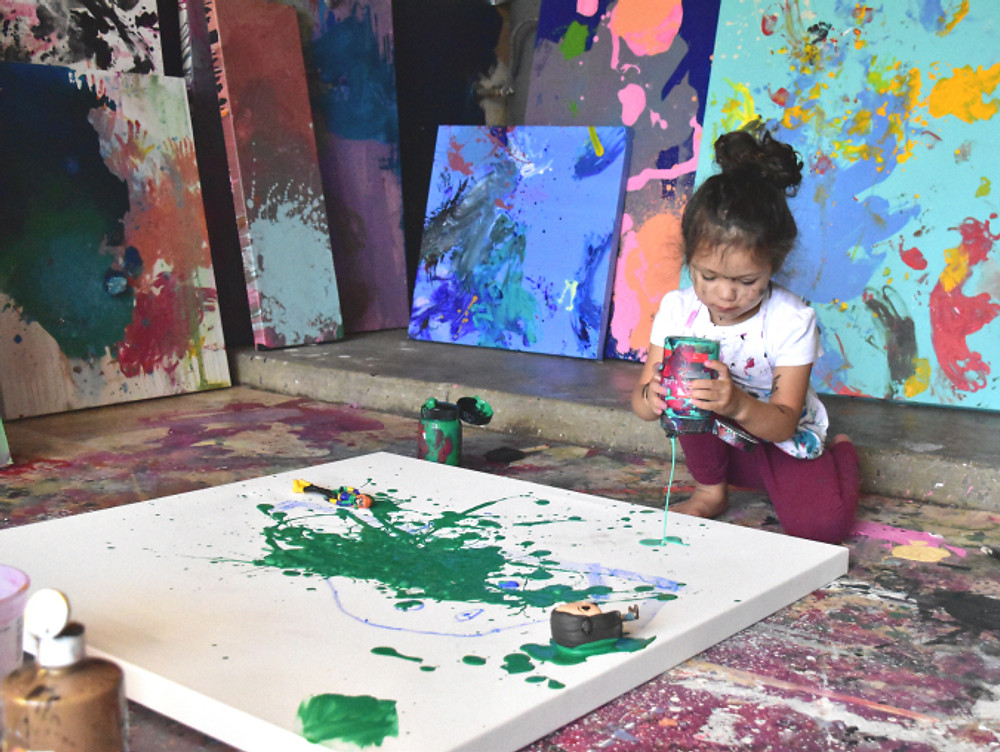 Four year old Apollonia working on a new acrylic painting in her studio.