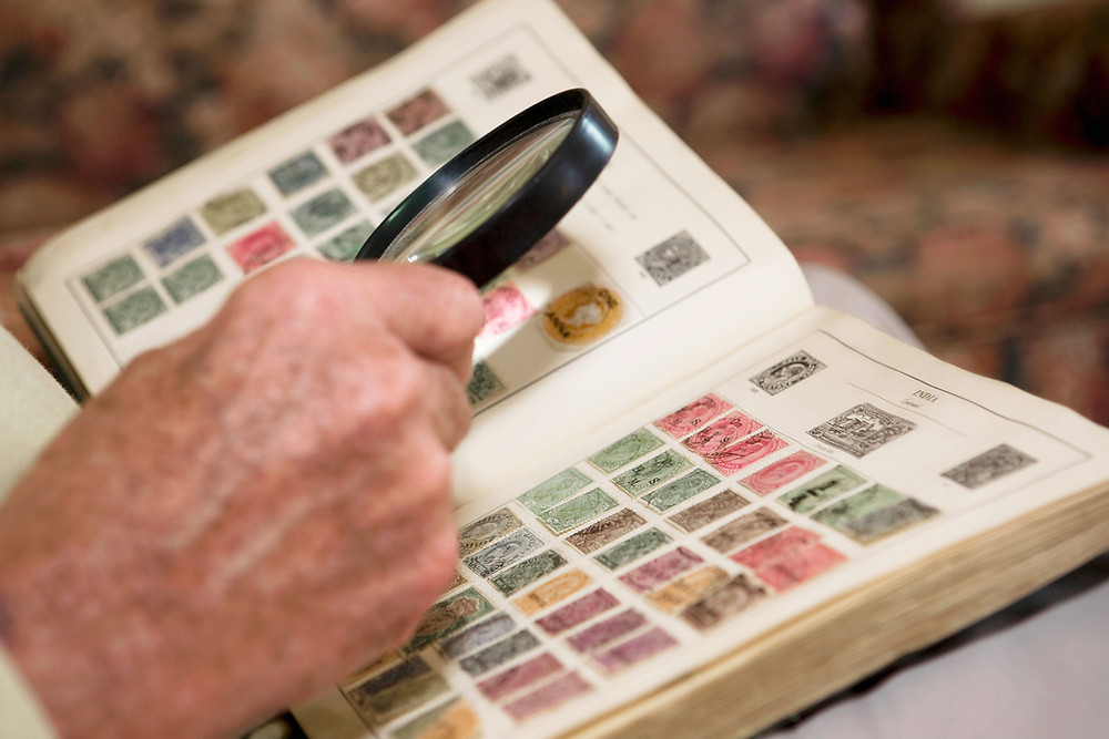 stamp collector with magnifying glass examining book of stamps