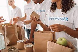 Volunteers packing items of food into food parcels.