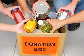 """A box with the text """"Donation Box"""" written across it. People are putting items of food into the box"""