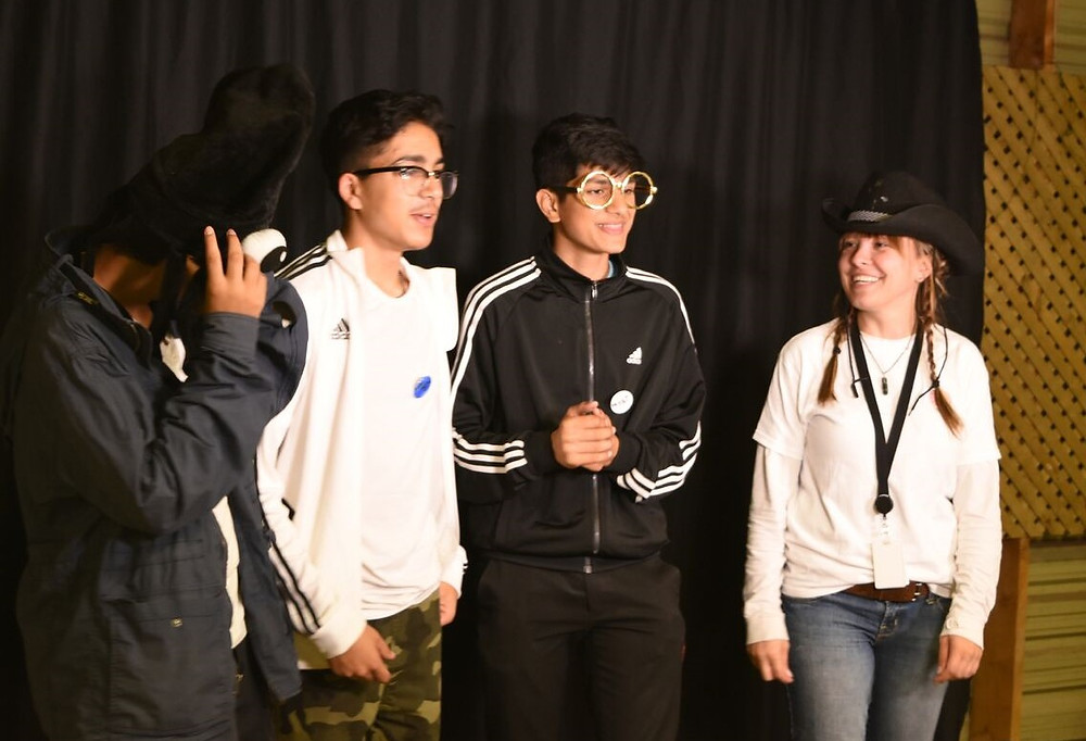 Teen-aged members of the Milton Youth Action Team on stage at the Fall Fair with their team facilitator Lily wearing funny hats and glasses.