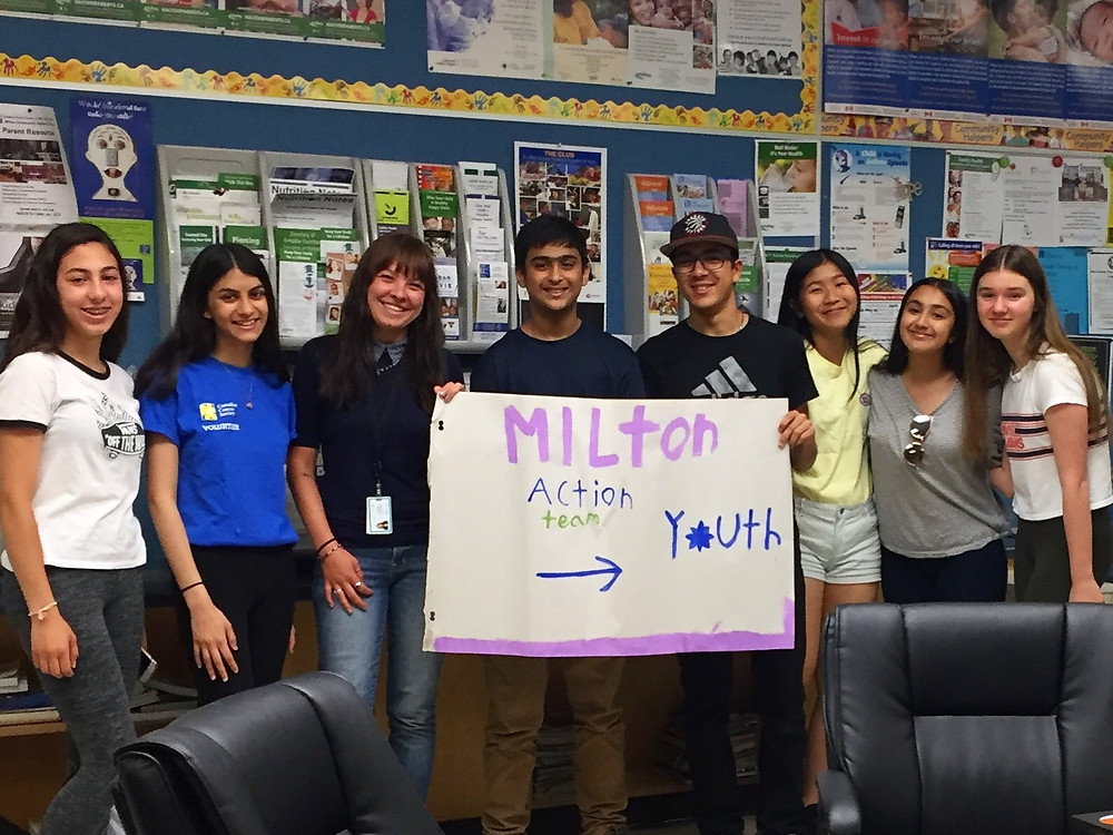 Group of 8 Milton Action Team Members in a classroom holding a sign that says Milton Action Team with an arrow to the word Youth
