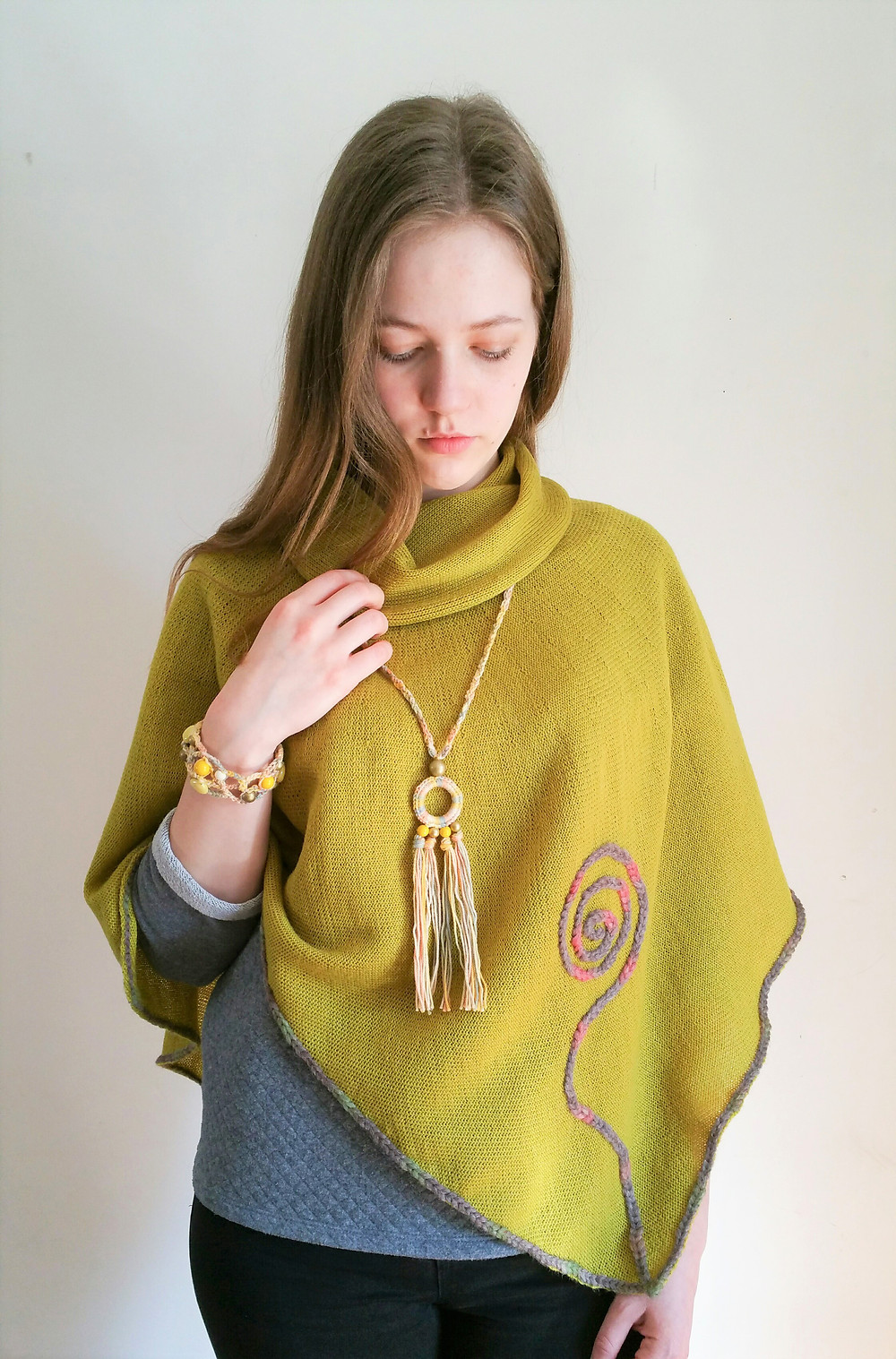 Yellow crocheted bracelet and pendant combined with green knitted Rune poncho.