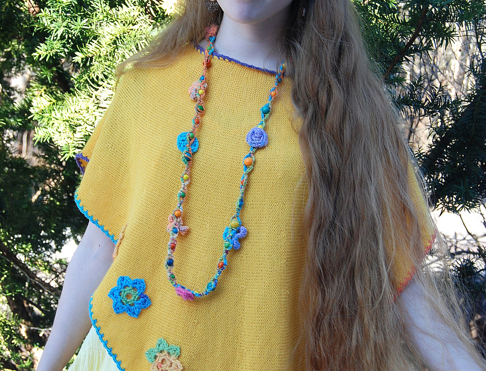 wearing yellow knitted triangel floral poncho with crocheted flower dedcorations