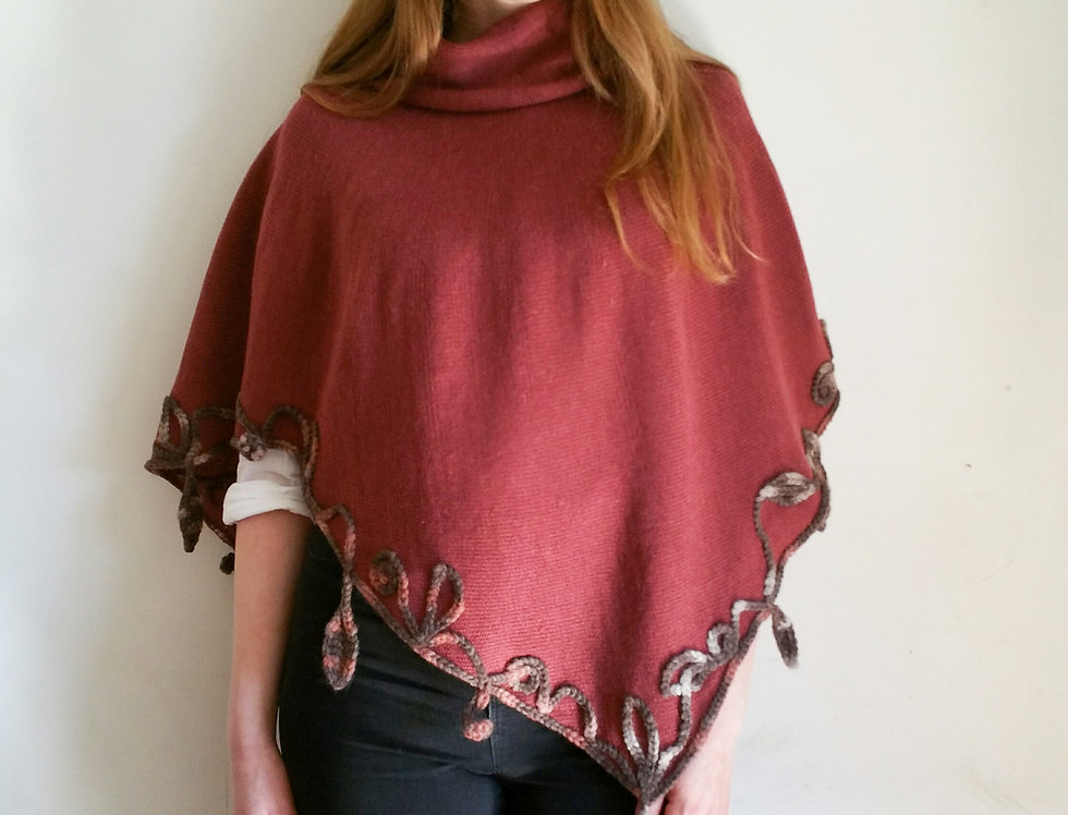 Wearing terracotta coloured knitted poncho with crocheted decoration