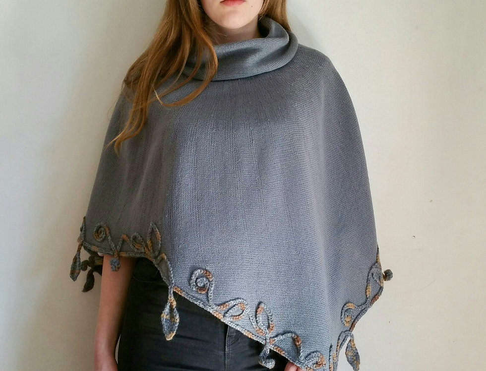Wearing grey coloured knitted poncho with crocheted decoration