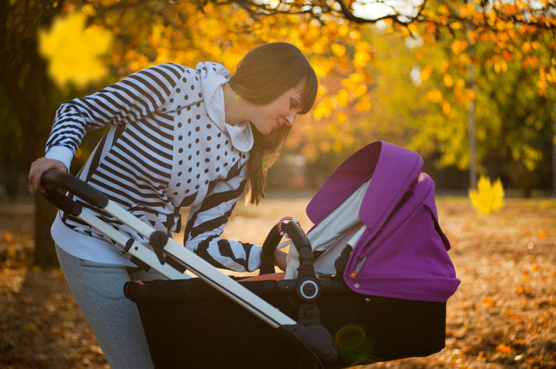 Nanny or Parents pushing a baby in a pushchair
