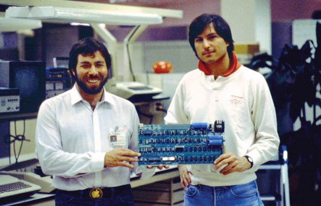 Воз и Джобс держат в руках материнскую плату Apple I