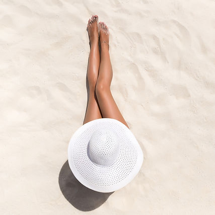 woman laying on the beach after spray tan