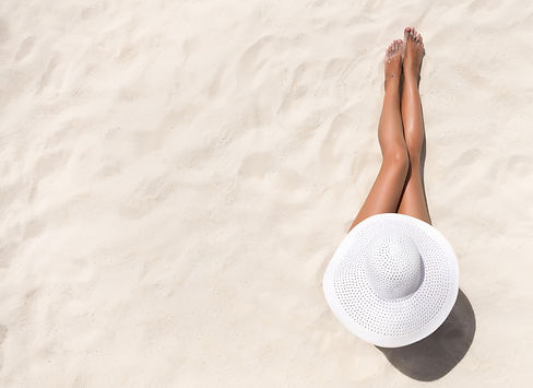 Woman with spray tan sitting on a sandy beach