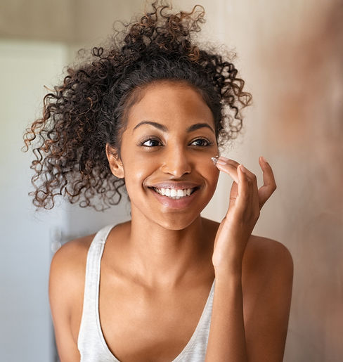 Young woman applying lotion to her face in mirror for healthy skin