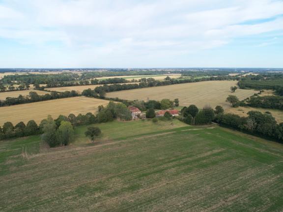 Photo par drone d'une propriété au coeur des cultures et de la forêt près de Châteauroux dans l'Indre 36