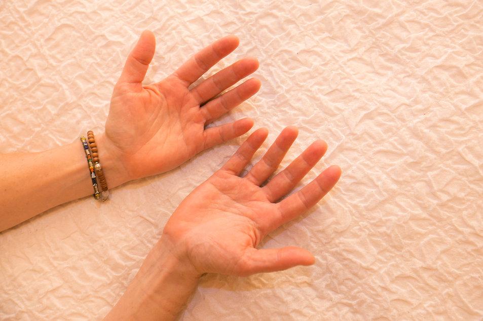 Hände von Cate Spinnler liegen auf einer Decke und sind bereit für eine Osteopathie oder Craniosacral Behandlung