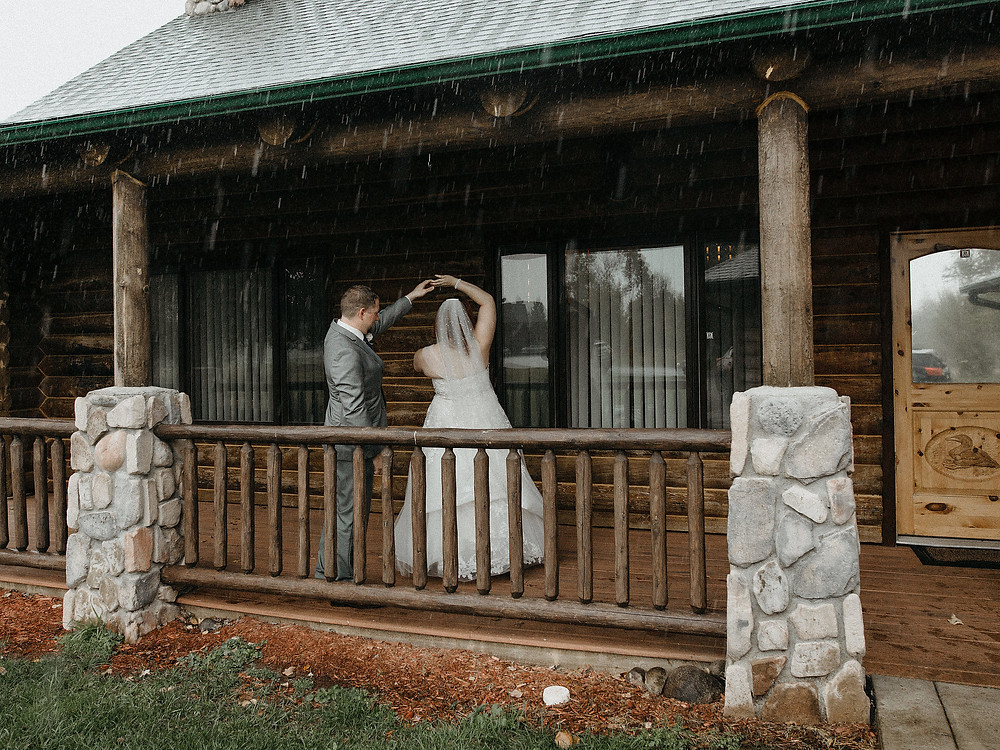 Duluth Wedding Photographer - The Autumn Dog Studio -  groom twirling bride on porch surrounded by rain