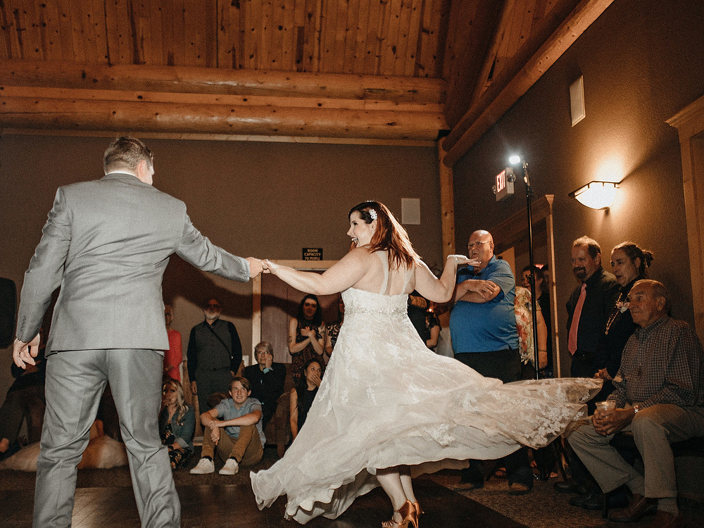 Duluth Wedding Photographer - The Autumn Dog Studio -  groom spinning bride outward during first dance