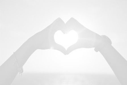 silhouette-of-hands-in-heart-shape-at-su