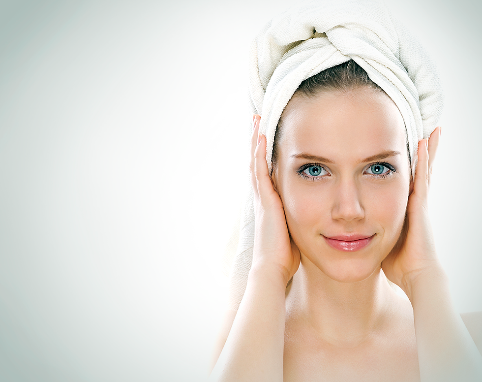 Woman with wet hair in towel holding towel with hands looking at the camera