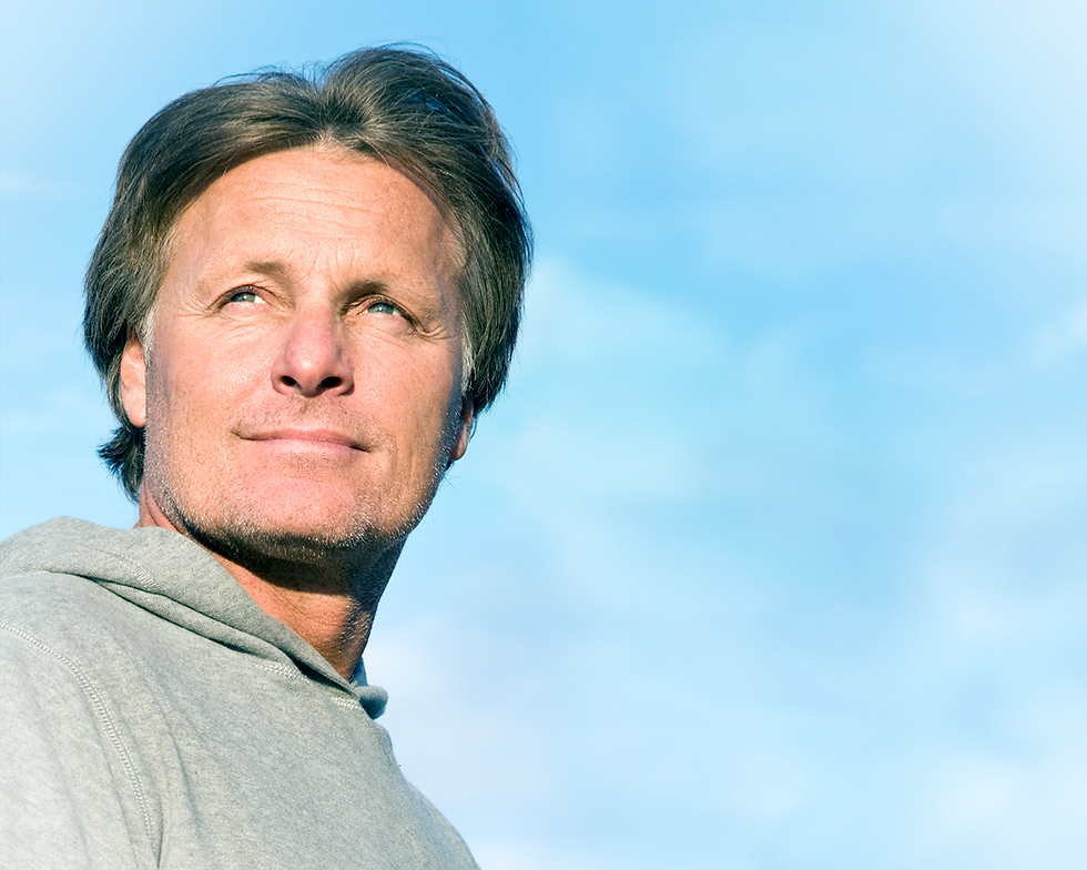 Middle aged man outdoors looking over the camera