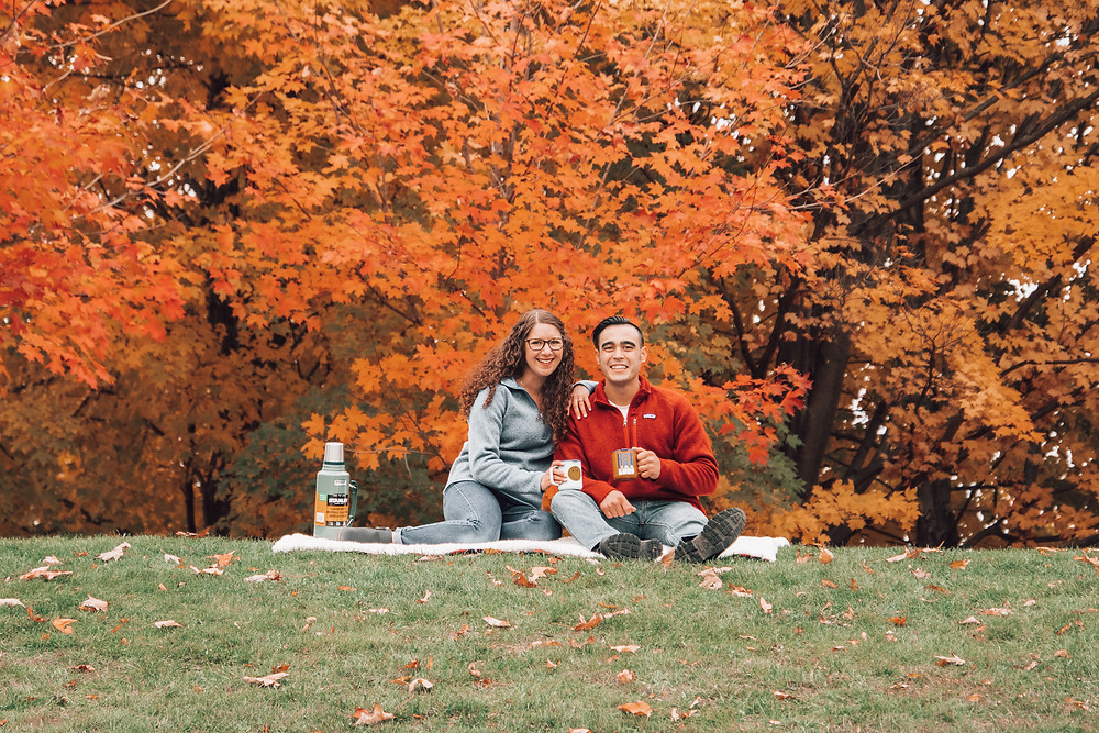 couple drinking hot cocoa in field of fall foliage