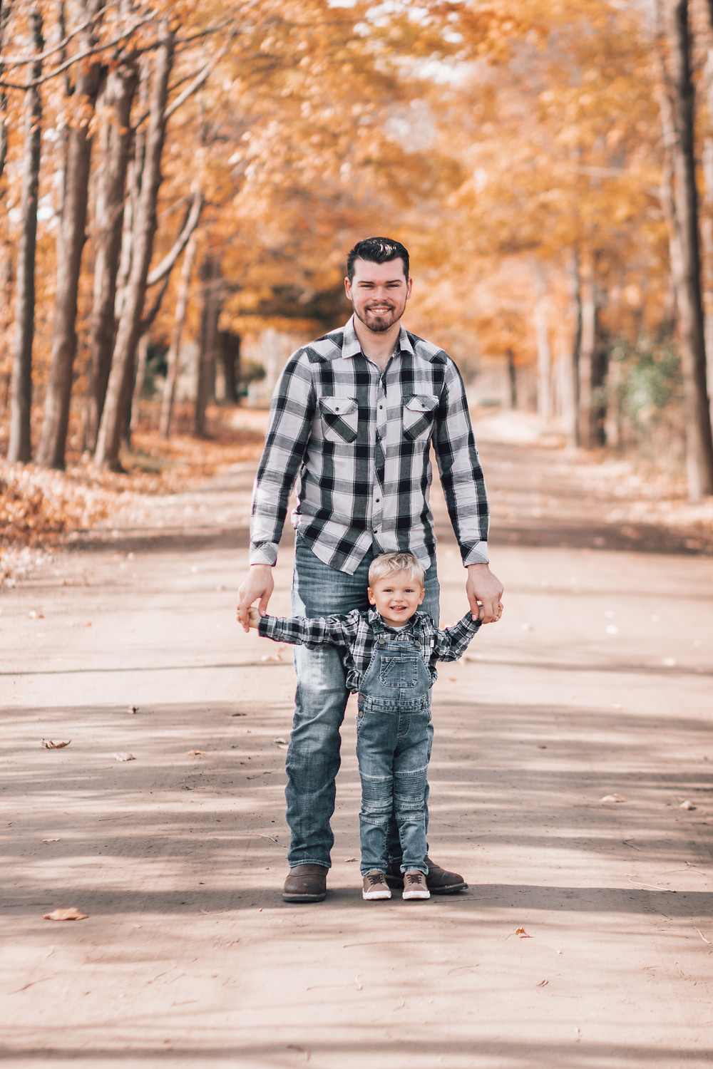 father with toddler son fall family portraits on dirt road