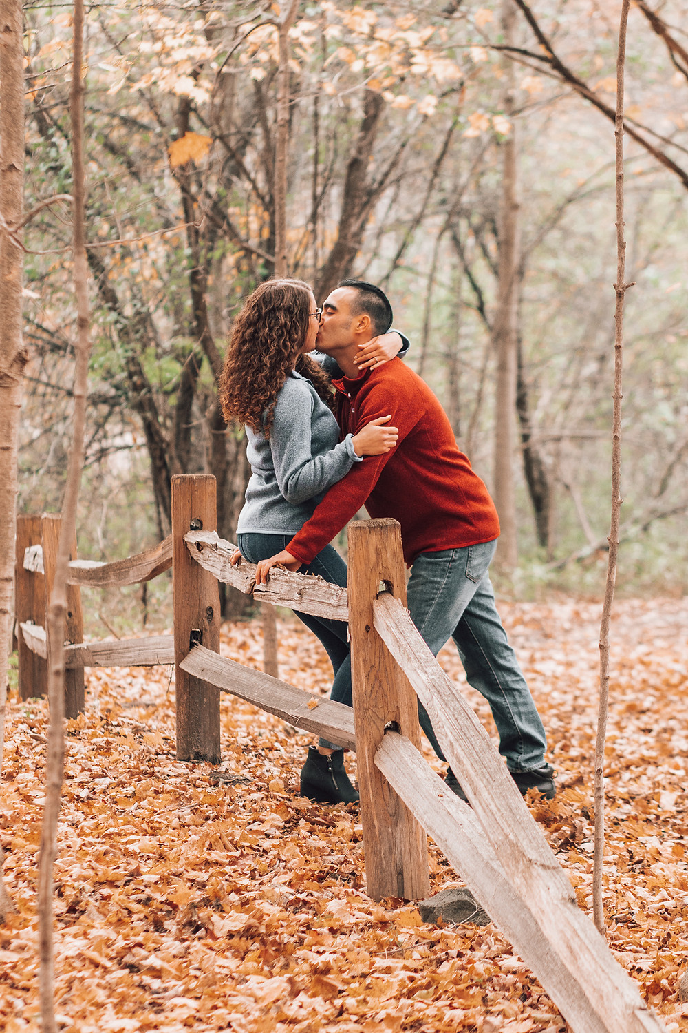 couple leaning against fence and kissing each other