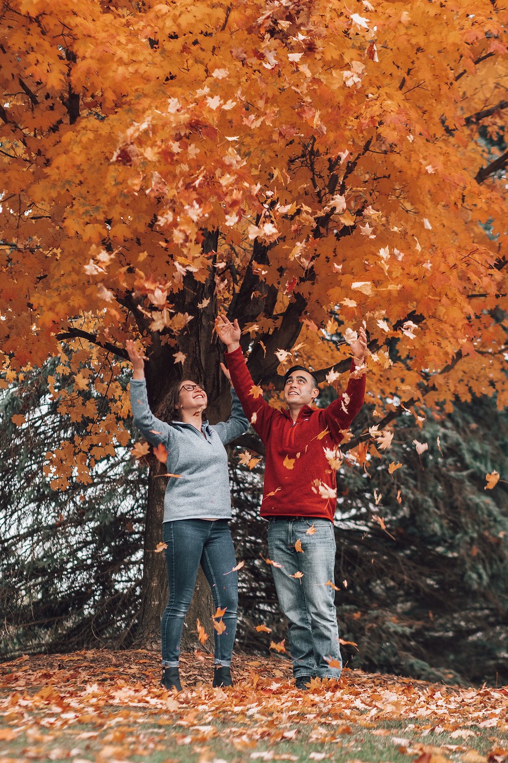 couple throwing leaves up in air during engagement session