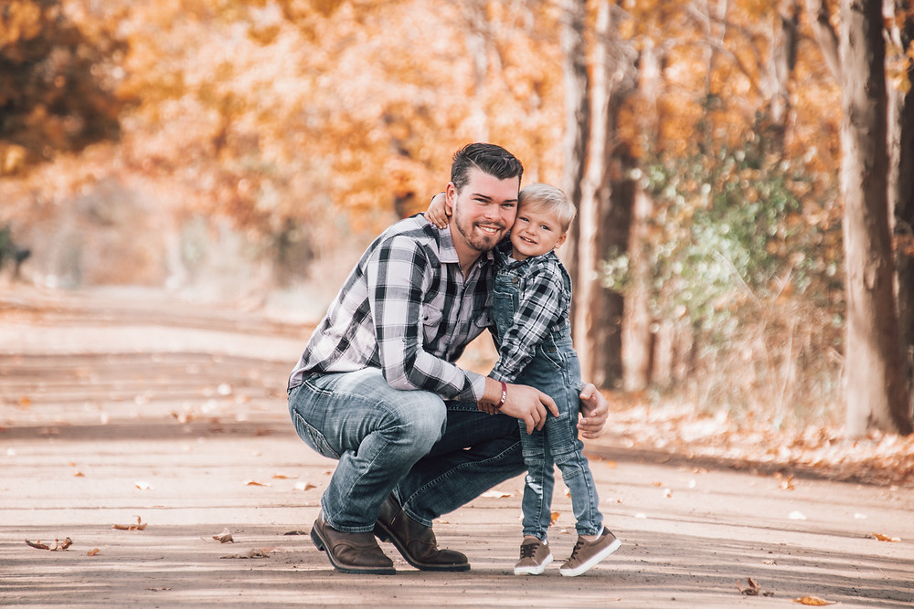 toddler son hugging father in fall family portraits