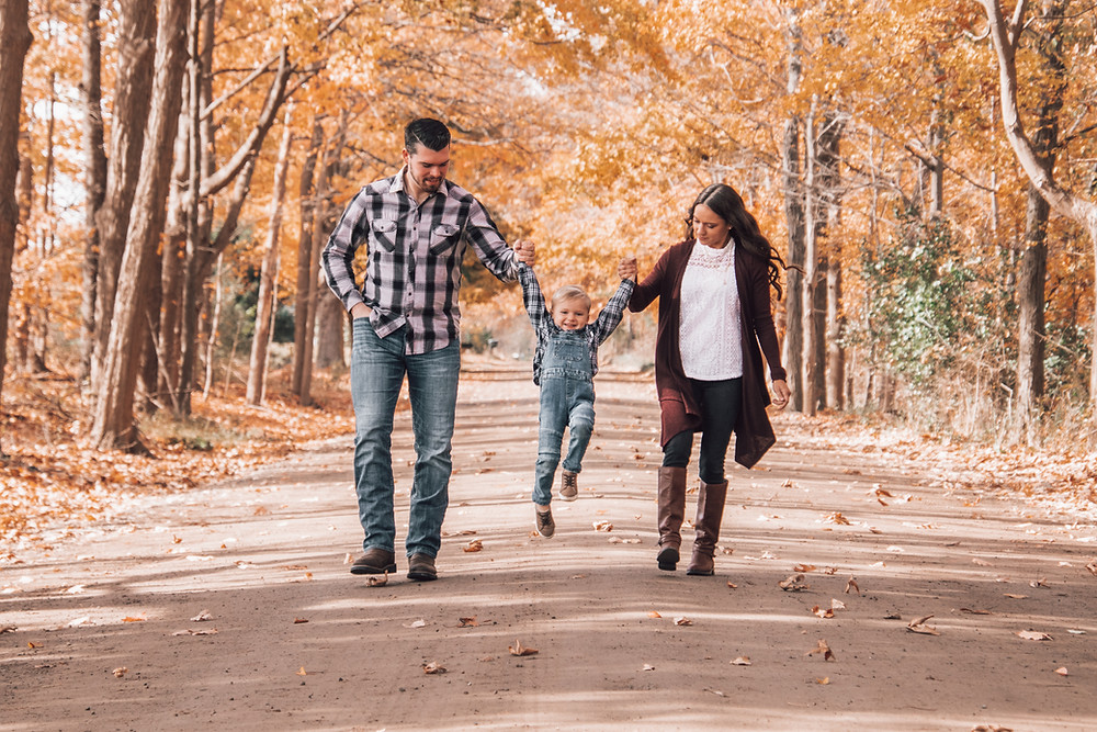 mom and dad swaying son in air down dirt road