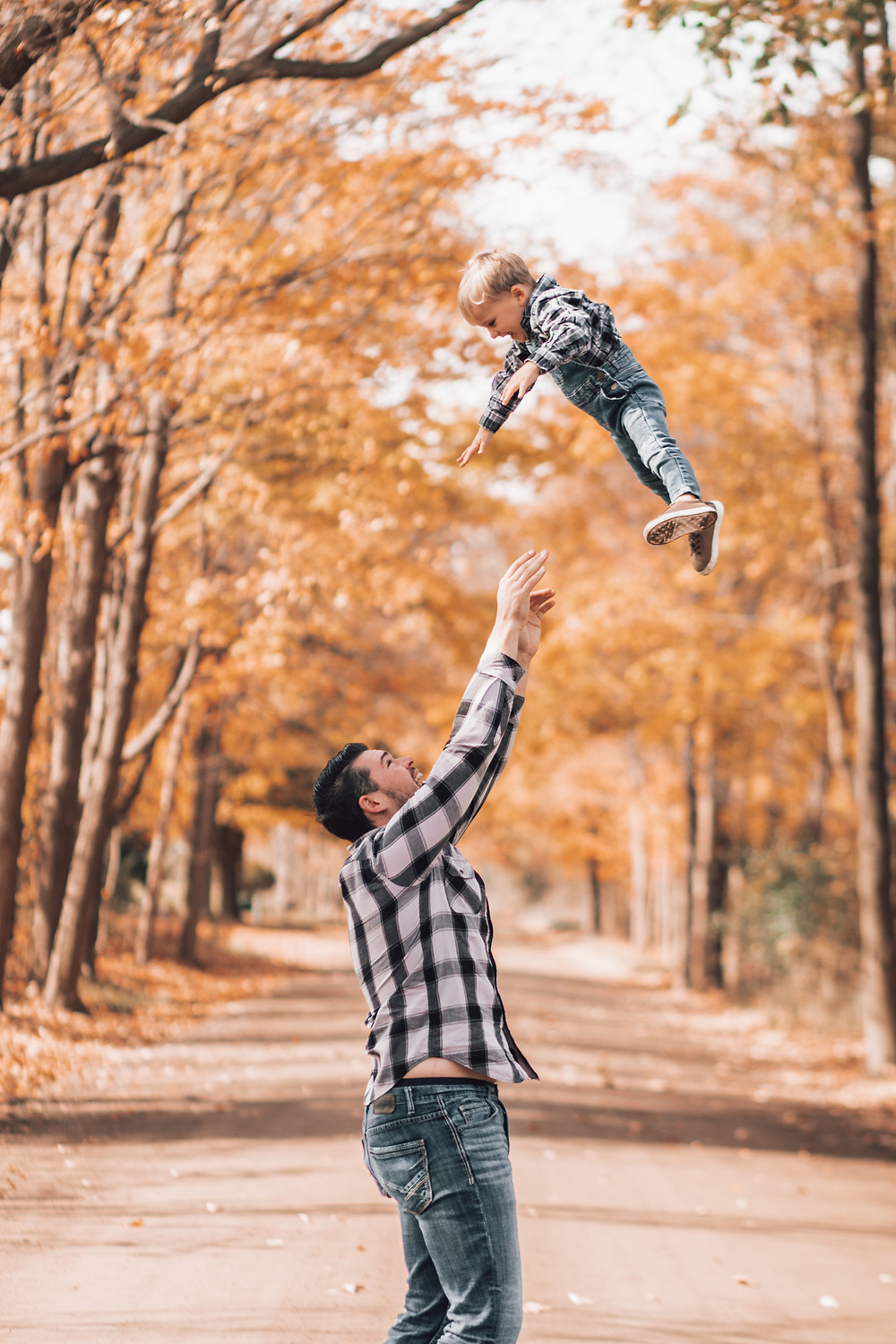 father tossing toddler son in air during fall family portraits