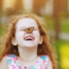 Funny laughing curly girl with a butterf