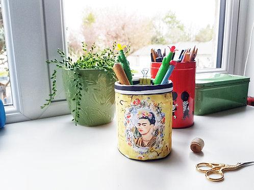 Frida Khalo in yellow floral, pen pot, storage bin.