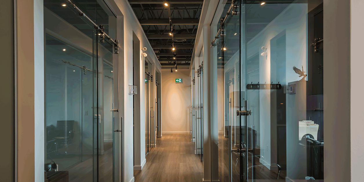 Inside of a commercial office space in Kelowna, managed and run by Worman Commercial.  This unit features a hallway with bright offices located on both sides with sliding glass doors and chrome fixtures