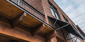 Worman Commercial built 2750 Richter Street, Kelowna, features exposed red brick and black trim.  On the east side of the building is all commercial spaces and on the west, residential rentals.