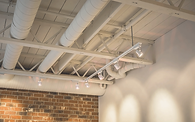 Ceiling of a commercial unit built by Worman Commercial with white panted exposed joists and track lighting.