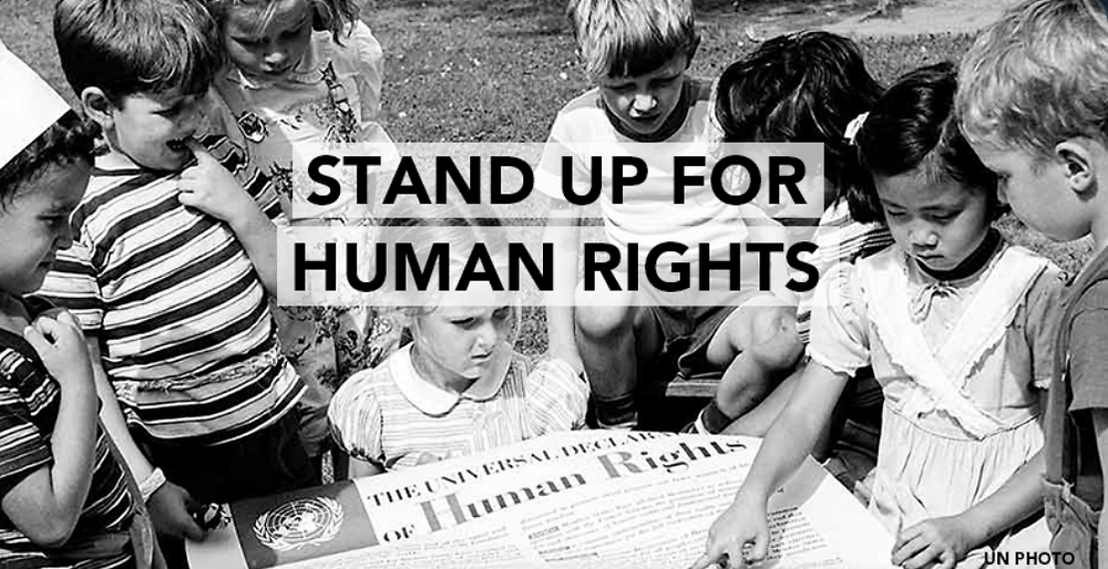 "Children holding the Universal Declaration of Human Rights . Captioned on the image is  the following words : ""Stand Up For Human Rights."""