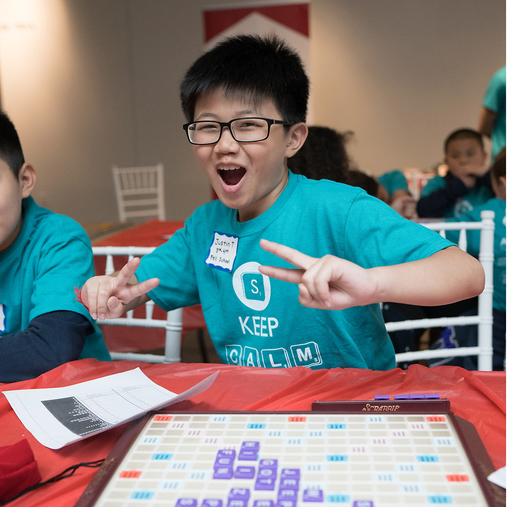 A pre-teen youth with short black hair and glasses holds his hands in V form with a triumphant smile. There is a Scrabble board with tiles in front of him.