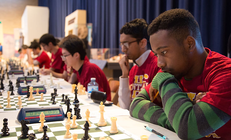 ASAP chess program - A teenager concentrates on a chess board. Beside him are other youth playing chess, lined up down a long table.