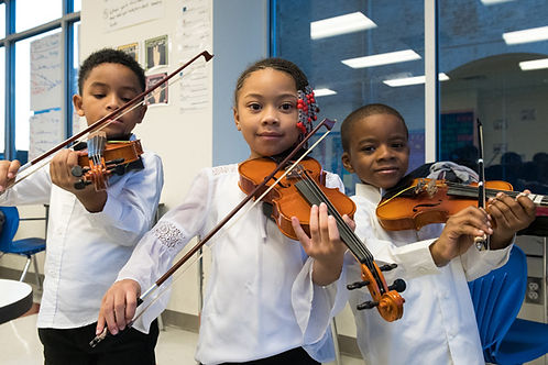 Three elementary age children pose holding violins and bows. They are all wearing white tops and black pants.