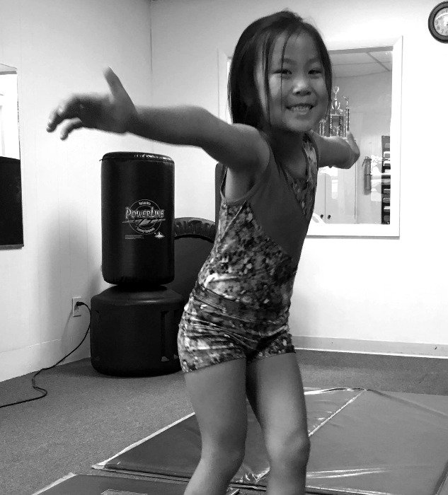Girl smiling standing pn a balance beam do gymnastcs