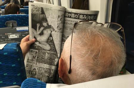 Peach & Peach, man reading newspaper on the Shinkansen, Bullet Train from Tokyo to Kyoto, Japan.