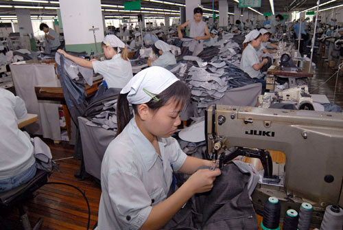 Workers sewing trousers for export in a textile factory, Shanghai, China.