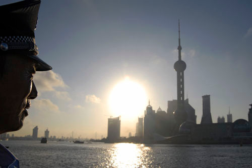 A police officer facing the Pudong skyline during the sunrise, Shanghai, China.