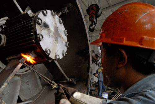 A worker welding a large turbine in a wharf in Pudong, Shanghai, China.