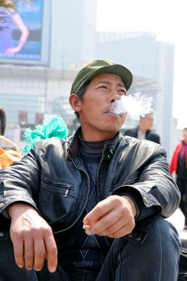 A migrant worker waiting for a train back to his home province, Shanghai, China.