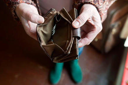 Maggie showing her almost empty purse, in her council flat in Moseley, Birmingham. She was asked to pay bedroom tax for one room, which she can't pay.
